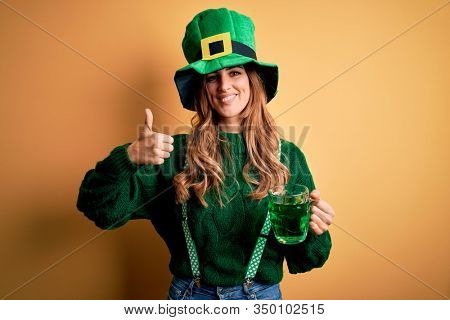 Beautiful woman wearing hat drinking jar of green beverage celebrating saint patricks day happy with big smile doing ok sign, thumb up with fingers, excellent sign