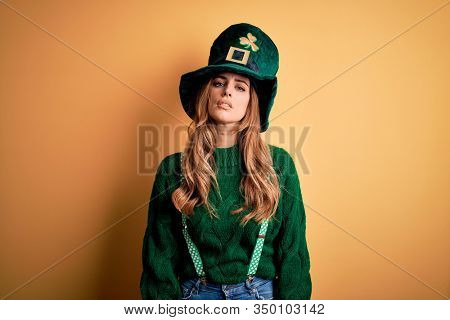 Beautiful brunette woman wearing green hat with clover celebrating saint patricks day Relaxed with serious expression on face. Simple and natural looking at the camera.