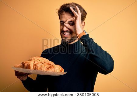 Young man with beard holding plate with croissants standing over isolated yellow background with happy face smiling doing ok sign with hand on eye looking through fingers