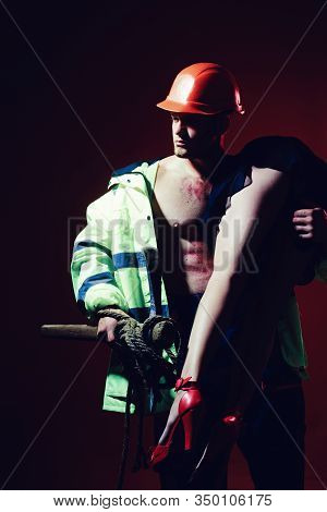 Having A Strong Sexual Appeal In Constructor Uniform. Muscular Man In Worker Uniform Holding Sexy Wo