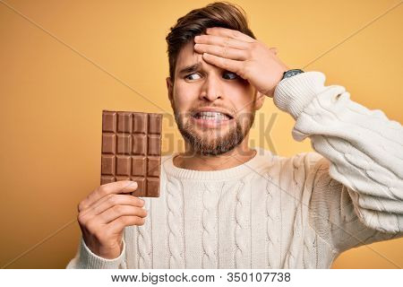 Young blond man with beard and blue eyes holding chocolate bar over yellow background stressed with hand on head, shocked with shame and surprise face, angry and frustrated. Fear and upset for mistake