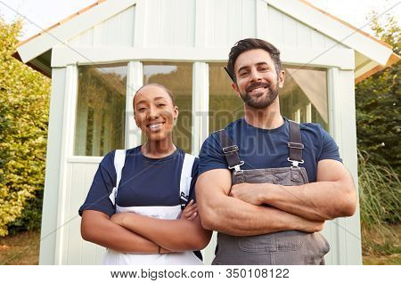 Male Carpenter With Female Apprentice Standing In Front Of Finished Outdoor Summerhouse In Garden