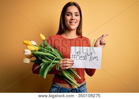 Beautiful woman celebrating mothers day holding best mom message and bouquet of tulips very happy pointing with hand and finger to the side