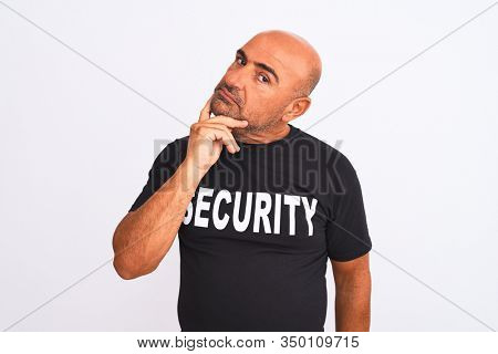 Middle age safeguard man wearing security uniform standing over isolated white background with hand on chin thinking about question, pensive expression. Smiling with thoughtful face. Doubt concept.