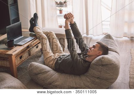 Handsome teenage guy watching movies while relaxing on modern couch in living room interior. Young man resting in soft chair at home.