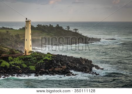 Nawiliwili, Kauai, Hawaii, Usa. - January 16, 2020: Yellow Ninini Lighthouse On Black Ocean-shore Ro