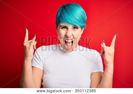 Young beautiful woman with blue fashion hair wearing casual t-shirt over red background shouting with crazy expression doing rock symbol with hands up. Music star. Heavy music concept.