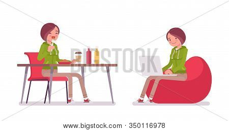 Young Woman Wearing A Hoodie Sitting And Working. Cute Lady In A Casual Hoody Having Lunch, Resting