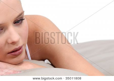 Sad blond woman in bed