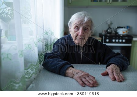 Lonely senior woman sitting by the window in his home.