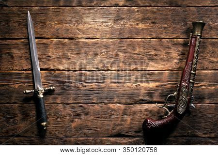 Ancient Weapon On Brown Wooden Table Background With Copy Space. Pirate Concept.