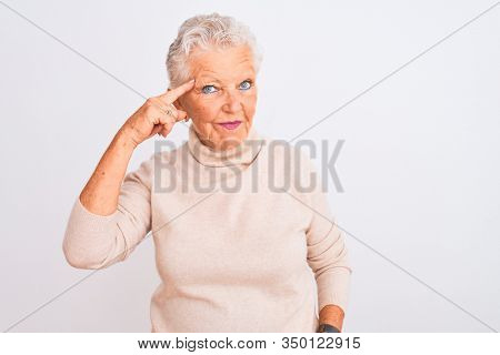 Senior grey-haired woman wearing turtleneck sweater standing over isolated white background Smiling pointing to head with one finger, great idea or thought, good memory
