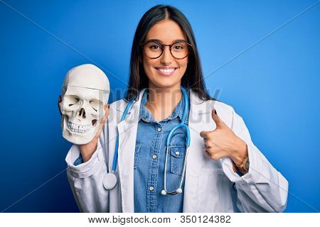 Young beautiful brunette doctor woman wearing coat holding human skull standing happy with big smile doing ok sign, thumb up with fingers, excellent sign