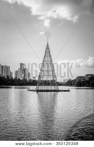 Black And White Photo Of A Floating Christmas Tree At A Lake, Made With A Steel Structure And Christ