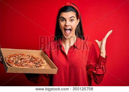 Young beautiful brunette woman holding delivery box with Italian pizza over red background very happy and excited, winner expression celebrating victory screaming with big smile and raised hands