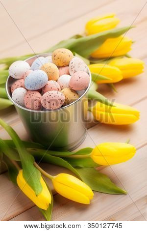 Pastel Easter egg candies with yellow tulips. Easter holiday concept.