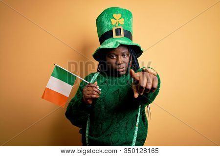 Plus size african american woman wearing green hat holding irish flag on saint patricks day pointing with finger to the camera and to you, hand sign, positive and confident gesture from the front