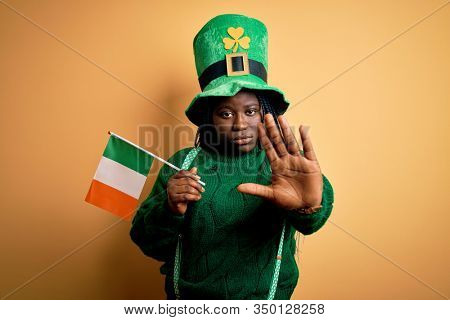 Plus size african american woman wearing green hat holding irish flag on saint patricks day with open hand doing stop sign with serious and confident expression, defense gesture