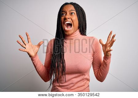 Young african american woman standing casual and cool over white isolated background crazy and mad shouting and yelling with aggressive expression and arms raised. Frustration concept.