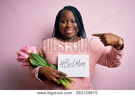 Plus size african american woman holding best mom message and tulips on mothers day with surprise face pointing finger to himself