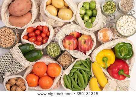 Fruits and vegetables in eco friendly reusable cotton bags, top view