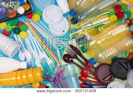 Disposable single use plastic objects such as bottles, cups, forks, spoons and drinking straws that cause pollution of the environment, especially oceans. Top view