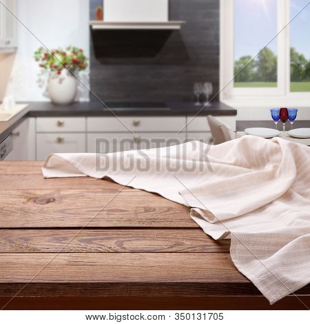 Empty Wooden Table With Tablecloth Near The Window In Kitchen. Napkin Close Up Top View Mock Up For
