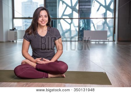 Photo Of Young Woman Practicing Yoga Indoor. Beautiful Girl Practice Yoga In Class. Yoga Studio Inst