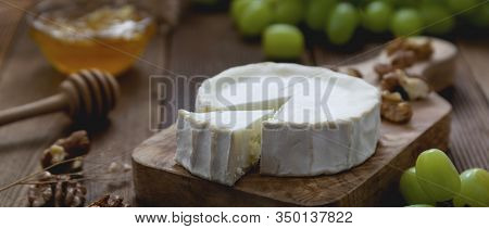 White, Round Cheeses On Wooden Background With Honey And Grapes. Dark Food Photography. Banner.