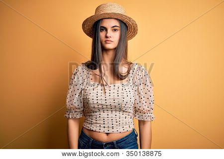 Young beautiful brunette woman wearing t-shirt and summer hat over yellow background with serious expression on face. Simple and natural looking at the camera.