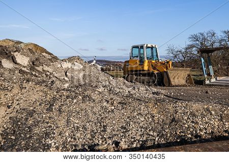 Disused Building Site With Bulldozer And A Pile Of Dirt On A Sunny Day.