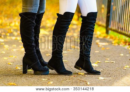 Two Unrecognizable Women Wearing Long Black Heeled Knee High Boots And Jeans. Autumn Fashion, Warm F