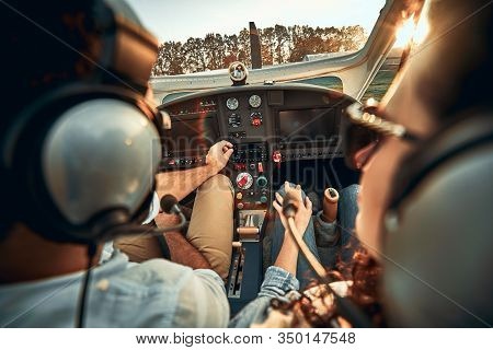 Rear View Of Pilot And Copilot In Private Cockpit Of Small Plane