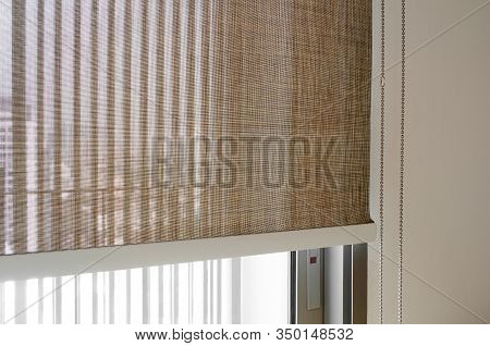 Closeup Brown Color Roller Blinds Curtains. Sunlight Through The Windows In The City. Soft Focus Ima