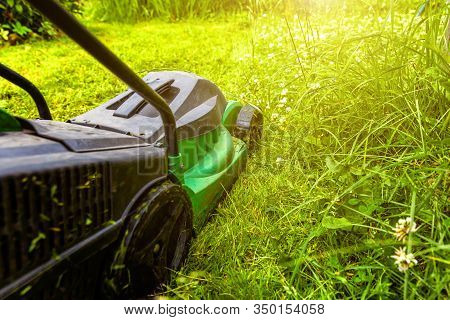 Man Cutting Green Grass With Lawn Mower In Backyard. Gardening Country Lifestyle Background. Beautif