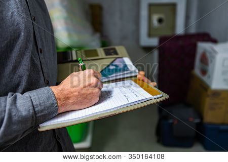 Inspector Holding A Notebook In His Hand During A Home Inspection In The Basement, Close Up And Sele