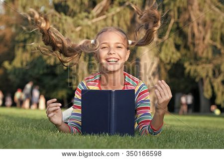 Getting Your Hairstyle Fly. Happy Child With Flying Hairstyle On Green Grass. Small Cute Girl Smile