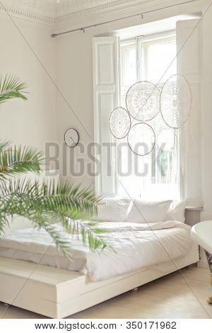 White Bed In Bright Livingroom In Scandinavian Style