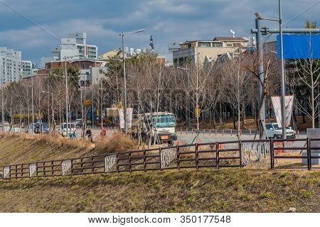 Daejeon, South Korea; January 30, 2020: Traffic On City Road Where Men Are Doing Street Work Near Ci