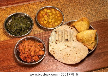Indian Various Food With Spice Curry And Naan Bread And Samosa On Wooden Table In Restaurant