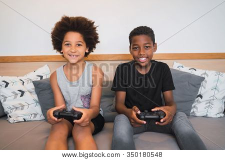 Two Brothers Playing Video Games At Home.