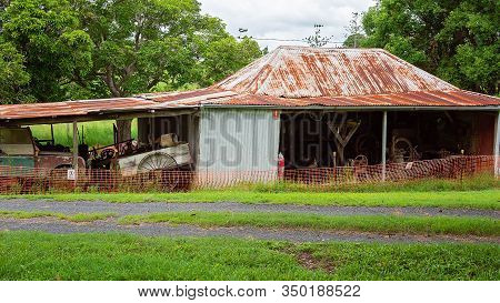 Old Dilapidated Shed Filled With Farm Vehicles And Implements Used By Early Settlers In The Past