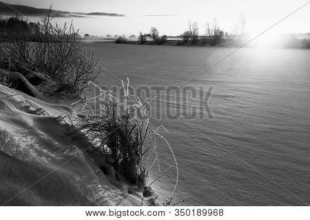 The Sun Rises Over The Icy River At The Rural Finland. The Sunlight Colors The Frosty Scenery Amber.