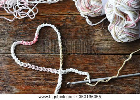 A Close Up Image Of A Crochet Heart Symbol And Metal Crochet Hook.