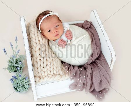 Adorable awake newborn in white diadem
