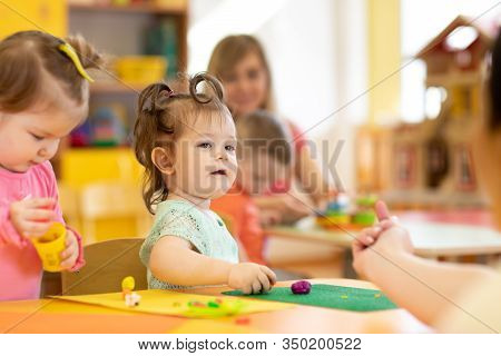 Nursery Children With Teacher Play Colorful Clay Toy In Daycare Or Kindergarten