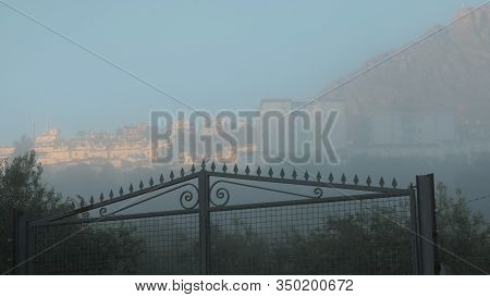 Hazy View Of White Andalusian Village Beyond Farm Gate On Foggy Morning
