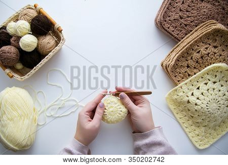 Female Hands Crocheting From Light Yellow Yarn Round Element. On A White Table Is A Crochet Process,