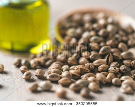 Close Up View Of Hemp Seeds And Hemp Oil On Brown Wooden Table. Hemp Seeds In Wooden Spoon And Hemp