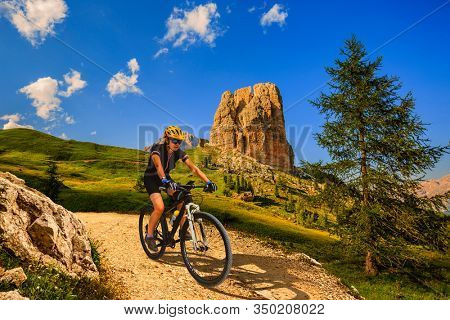 Tourist cycling in Cortina d'Ampezzo, stunning rocky mountains on the background. Woman riding MTB enduro flow trail. South Tyrol province of Italy, Dolomites.